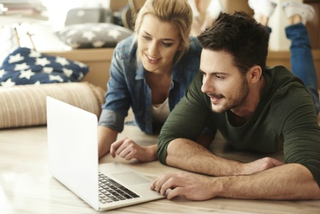 smiling man and woman on carpet looking at lap top