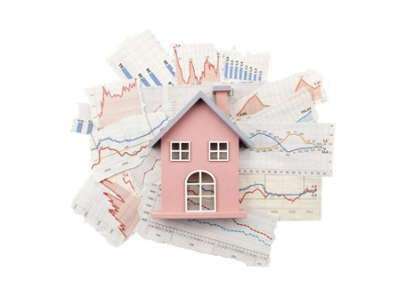 real estate market report concept with pink model house sitting on paper graphs