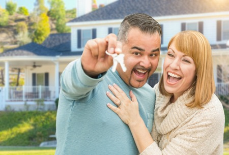 smiling man and woman holding house keys
